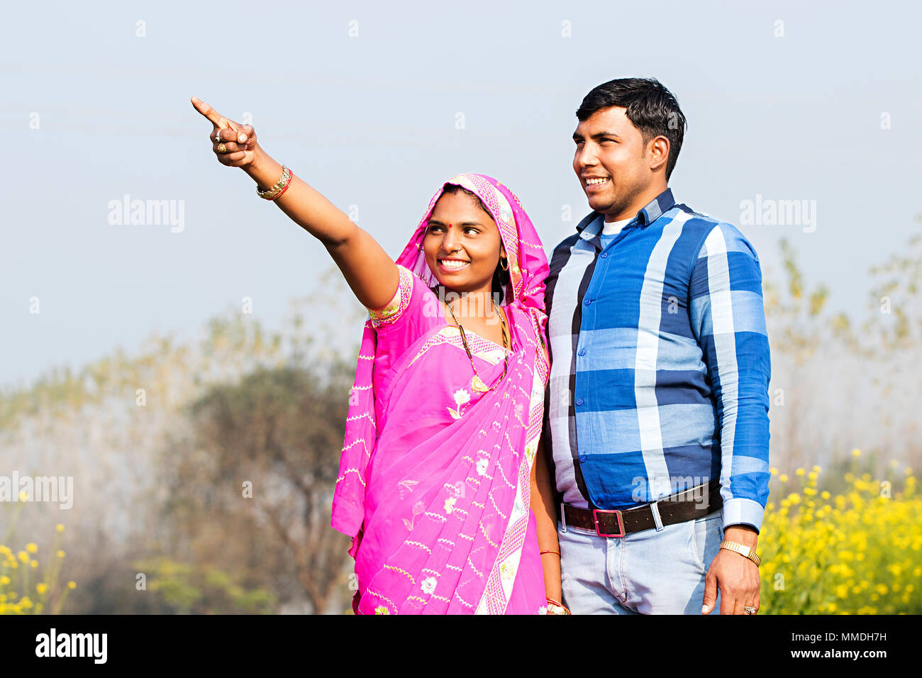 Happy rural farmer married couple pointing finger showing field village