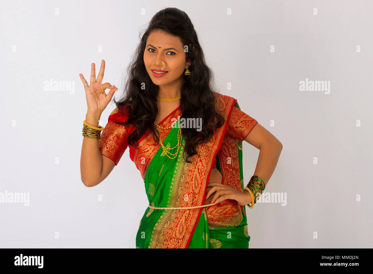 Stylish Indian woman in silk saree and nose ring with OK gesture in a front pose Stock Photo