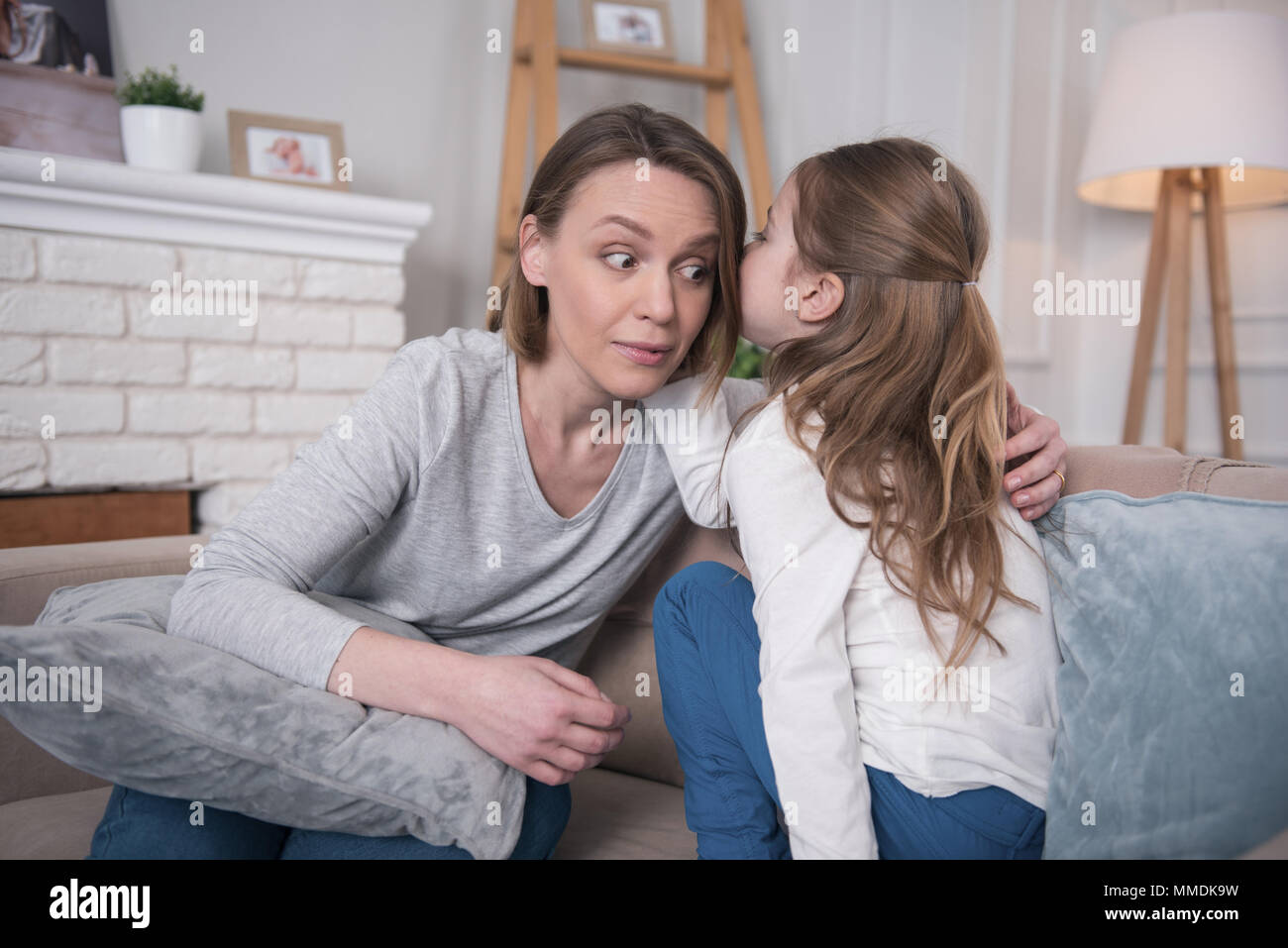 Inspired girl telling secrets to her mom - Stock Image
