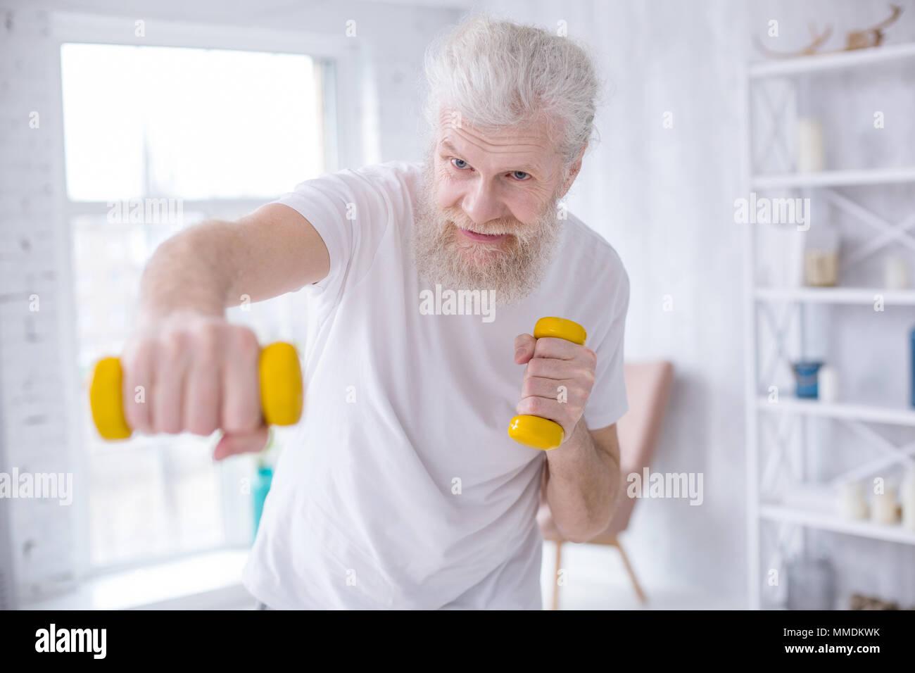 Elderly bearded man practicing jabs with dumbbells - Stock Image