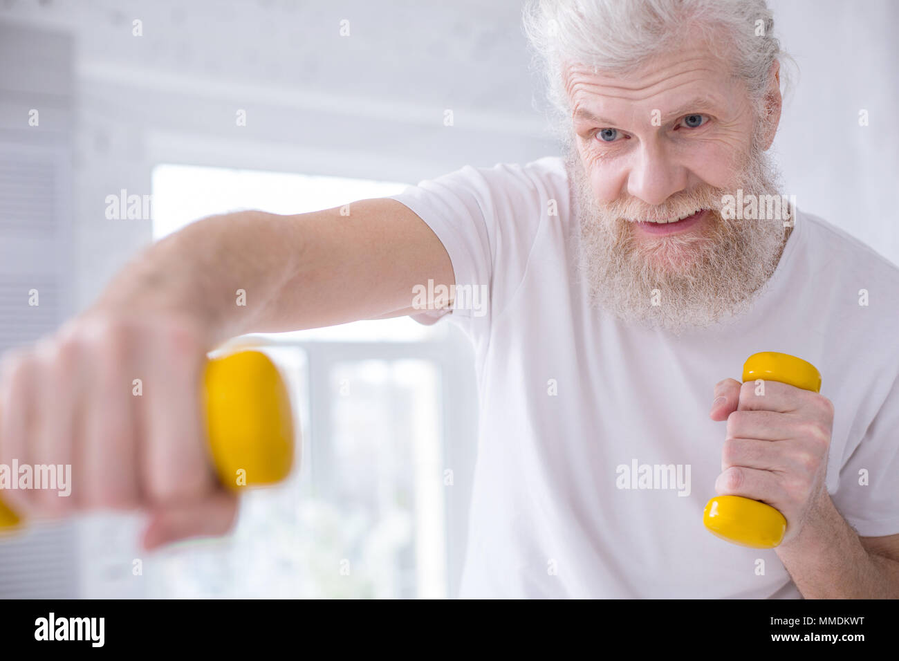 Close up of senior man working out with dumbbells - Stock Image