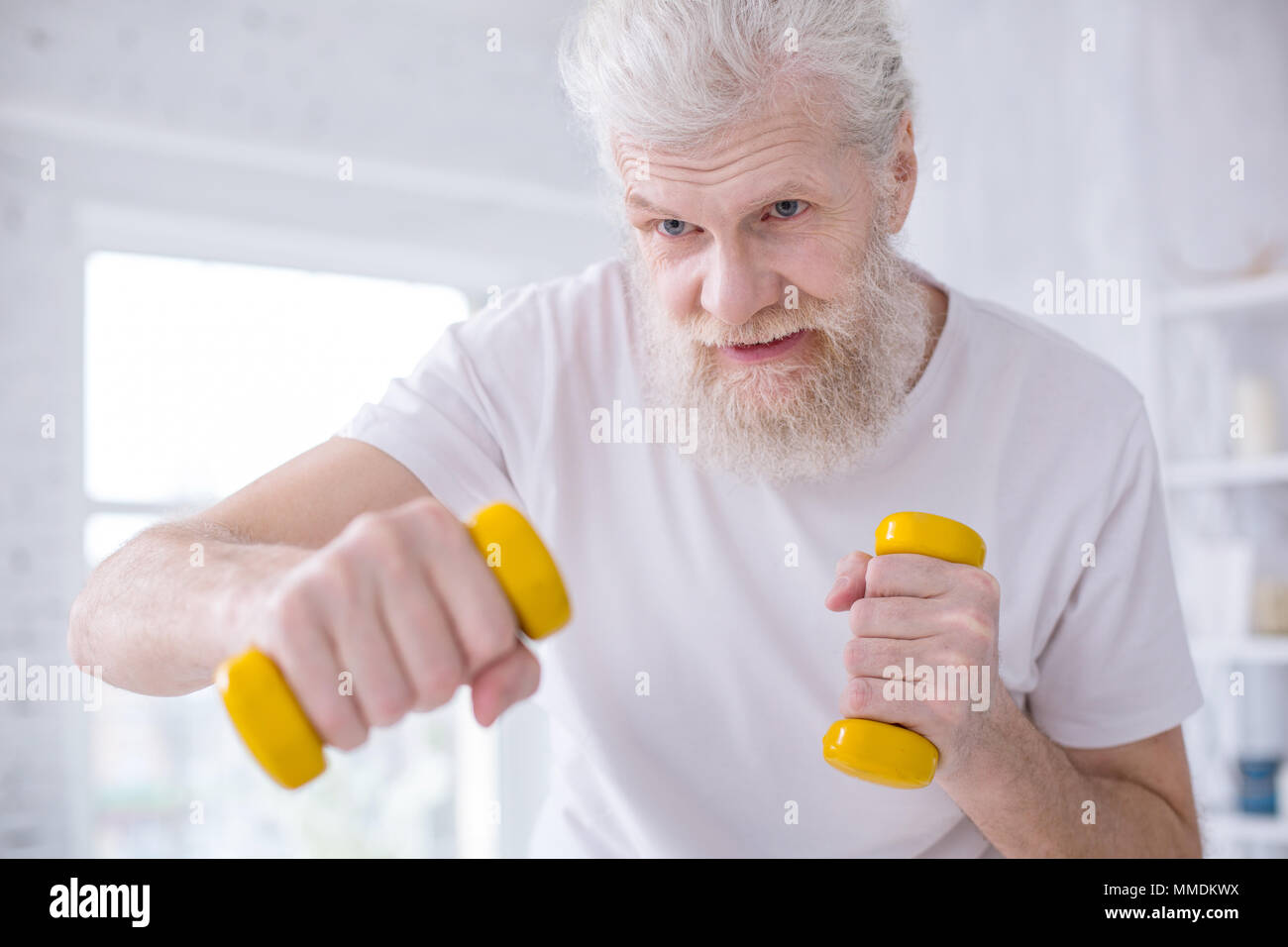 Close up of elderly man practicing boxing jabs with dumbbells - Stock Image