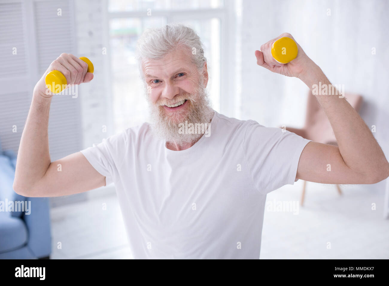 Fit elderly man showing biceps while holding dumbbells - Stock Image