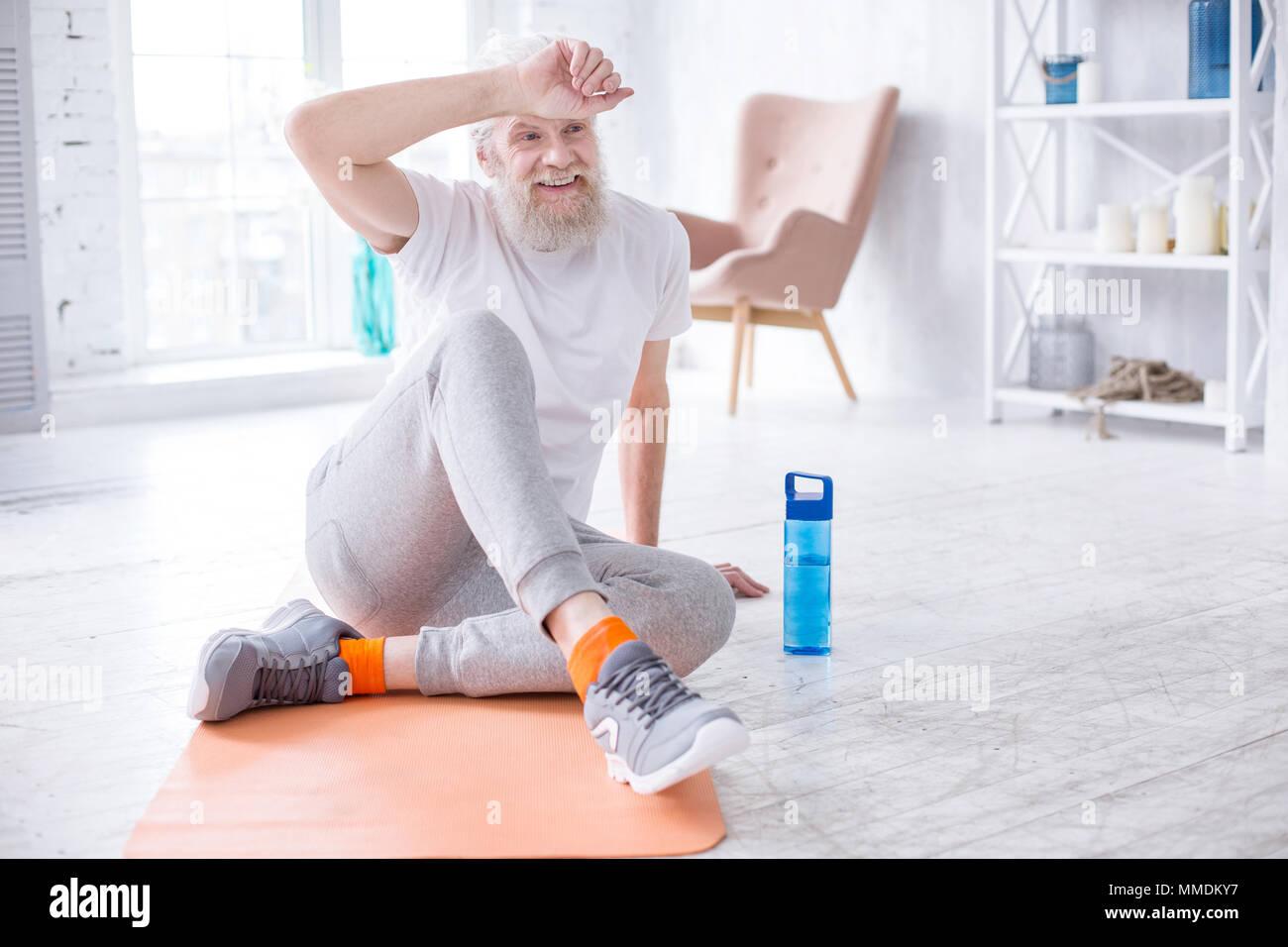 Charming senior man having rest after exercising - Stock Image
