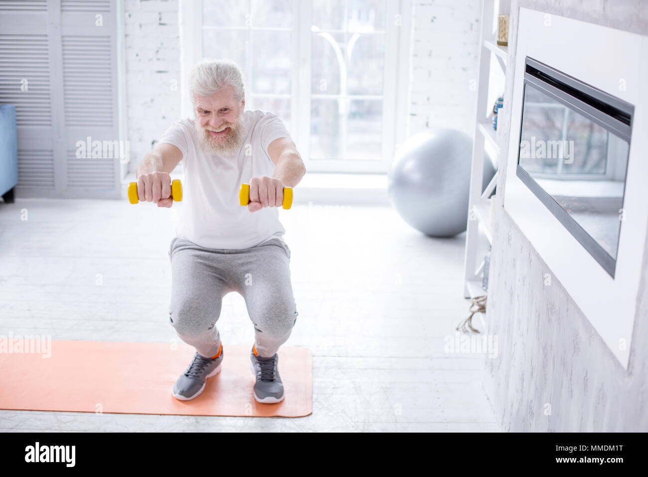 Handsome elderly man holding dumbbells and doing squats - Stock Image