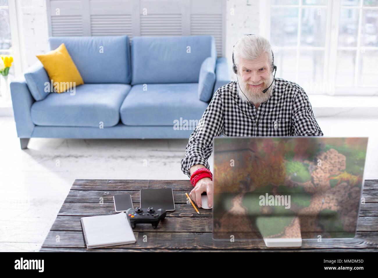 Charming elderly man enjoying a multiplayer online game - Stock Image
