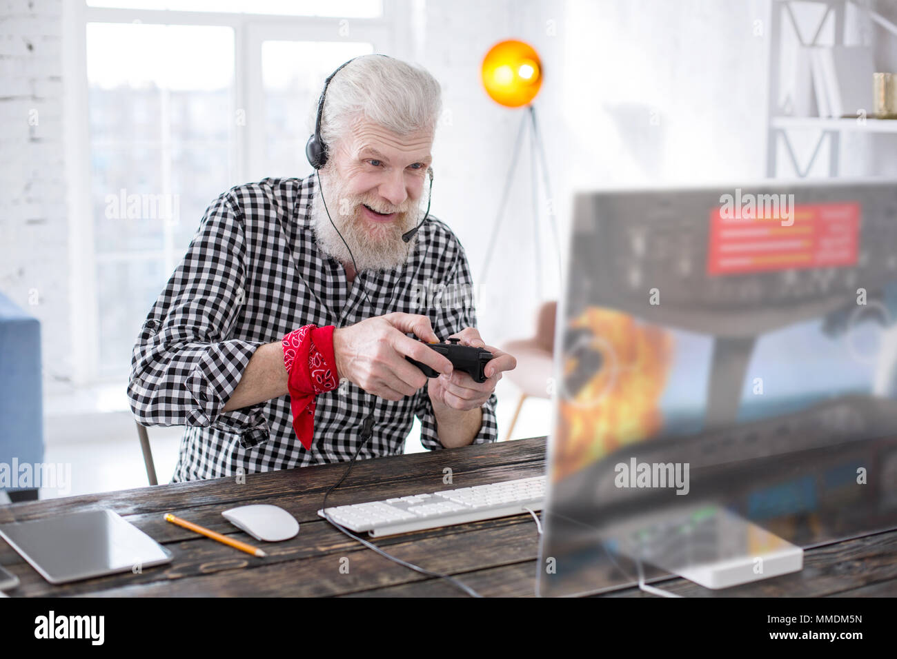 Excited senior man playing online game with controller - Stock Image