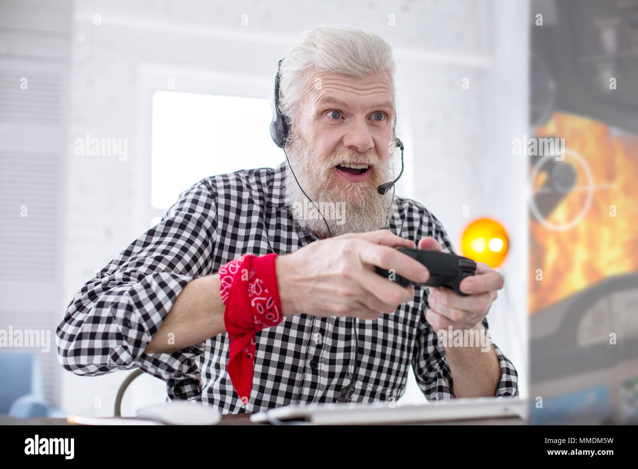 White-haired senior man being excited about playing video game - Stock Image