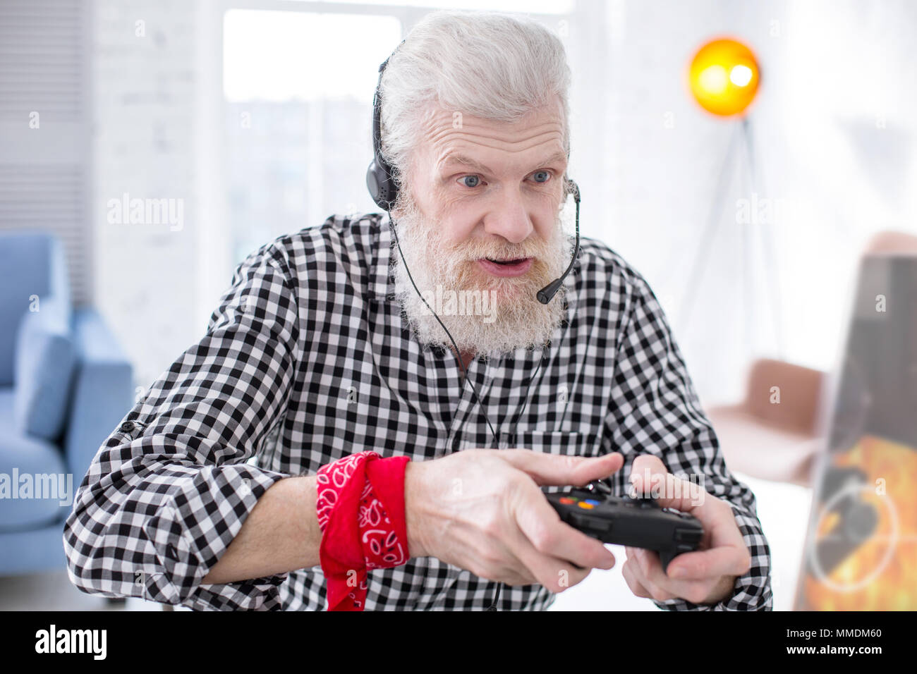 Bearded senior man being immersed into playing video game - Stock Image