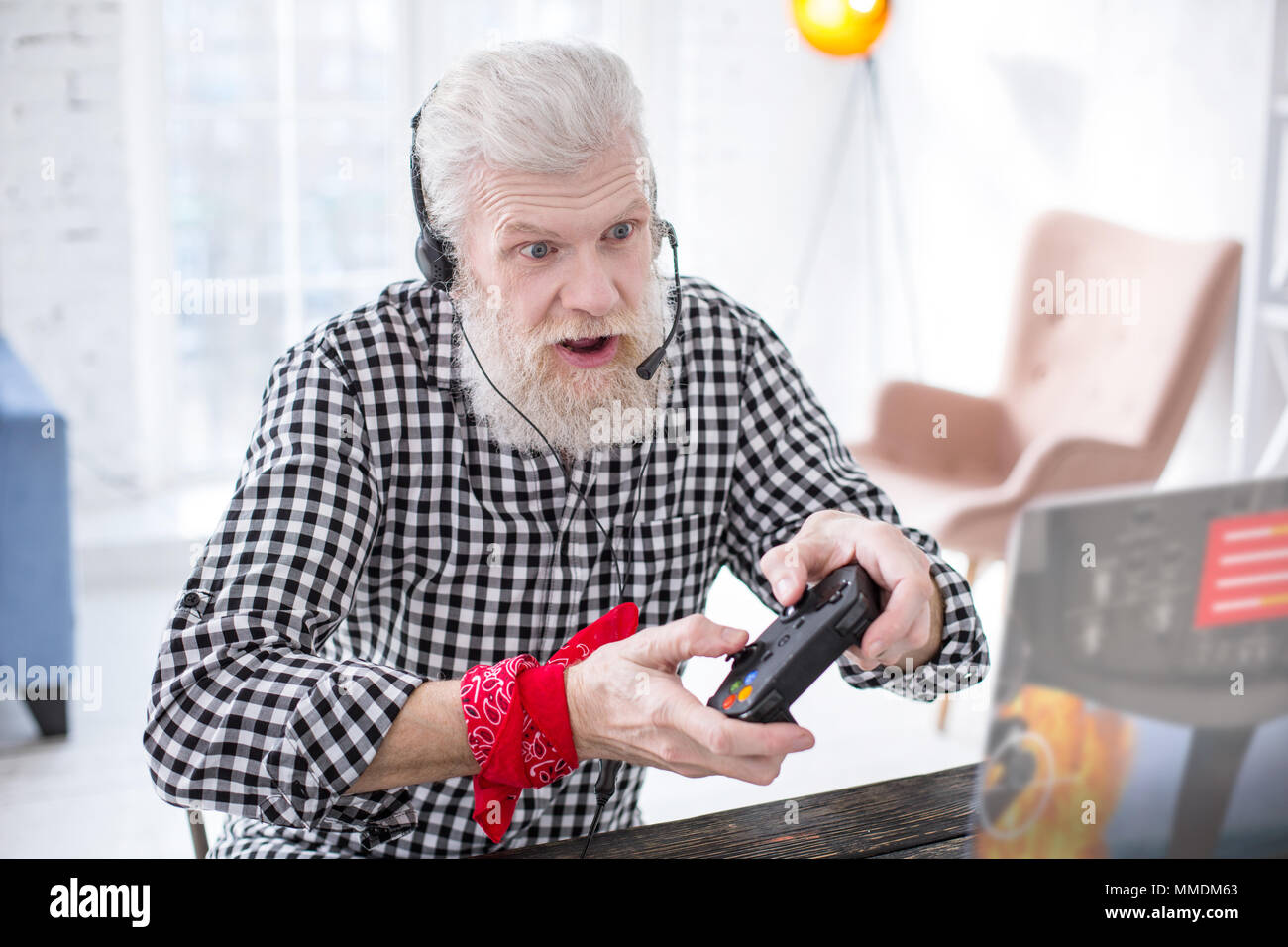 White-haired elderly man playing video game excitingly - Stock Image
