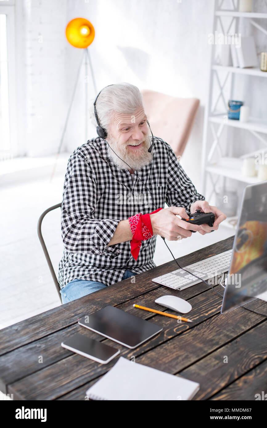 Upbeat senior man having fun while playing video game - Stock Image