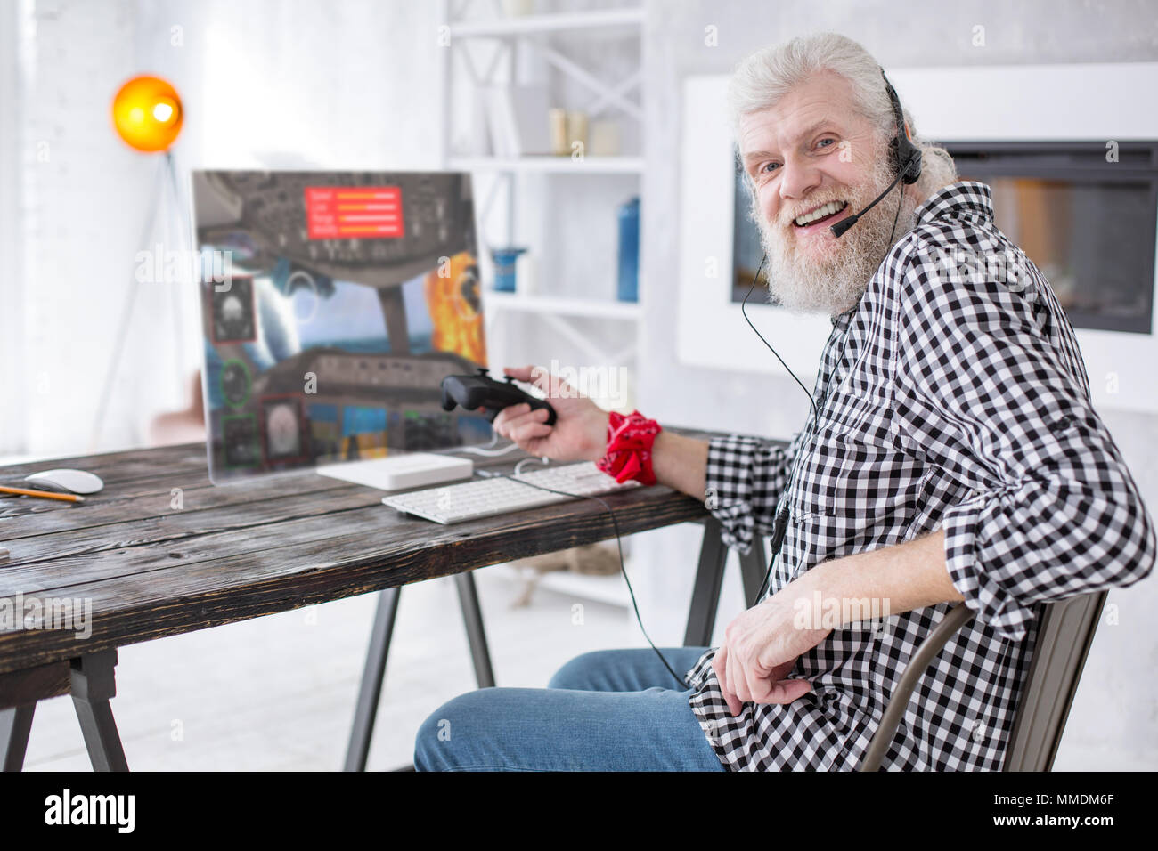 Cheerful senior man posing while playing aircraft battle simulator - Stock Image