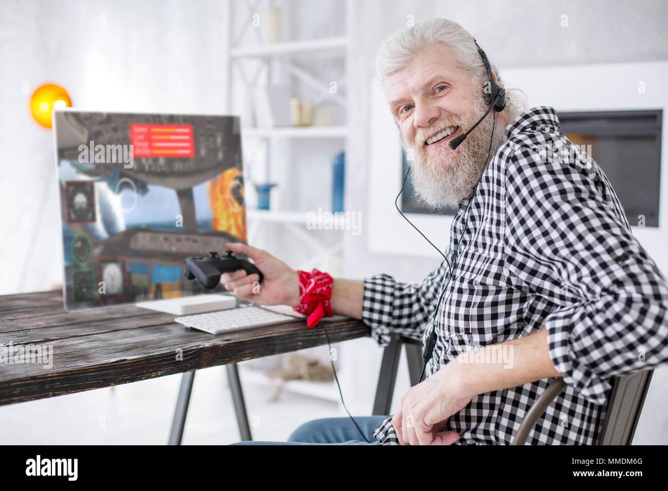Joyful elderly man posing while taking break at playing game - Stock Image