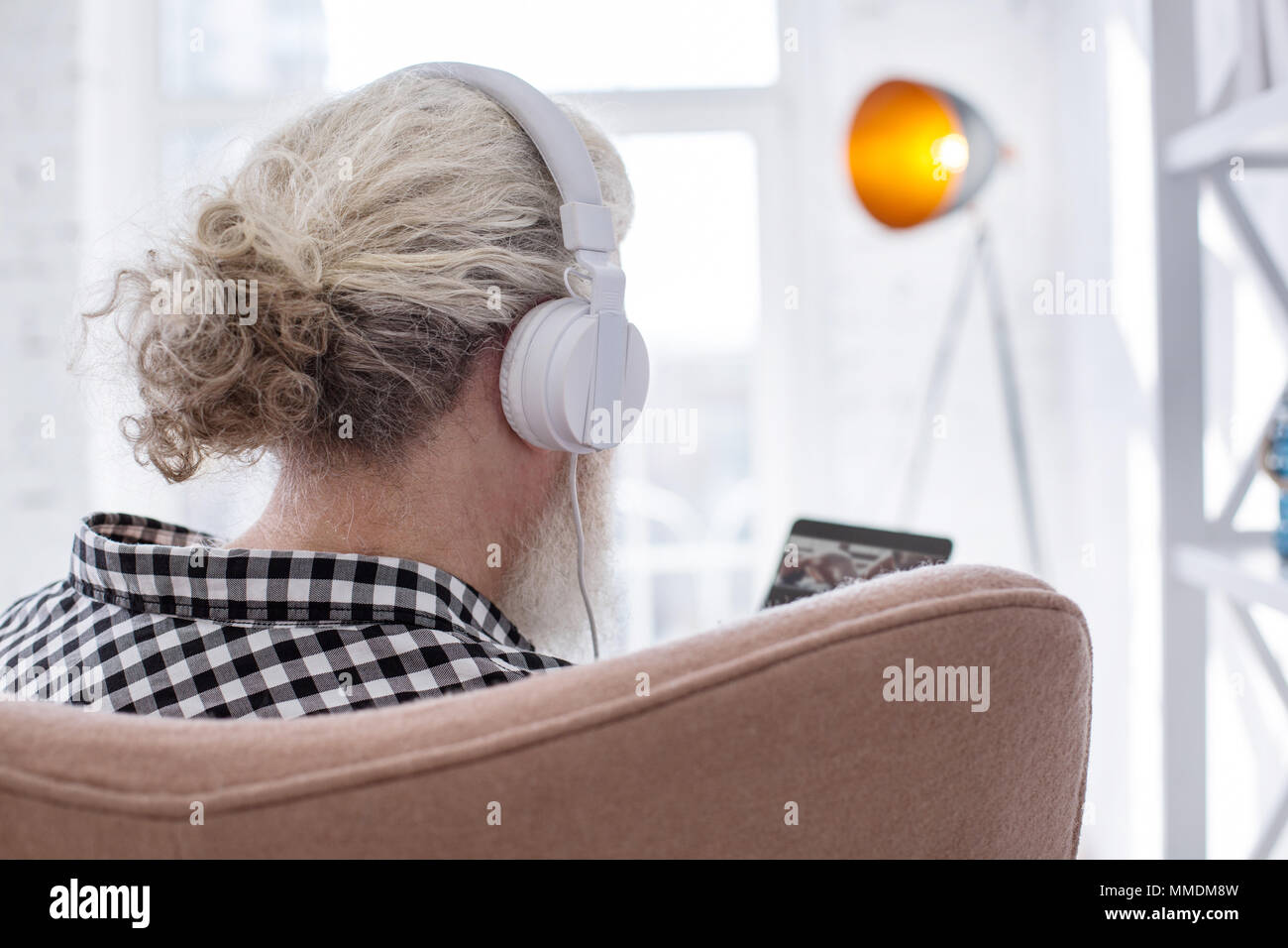 Pleasant senior man looking through his playlist - Stock Image
