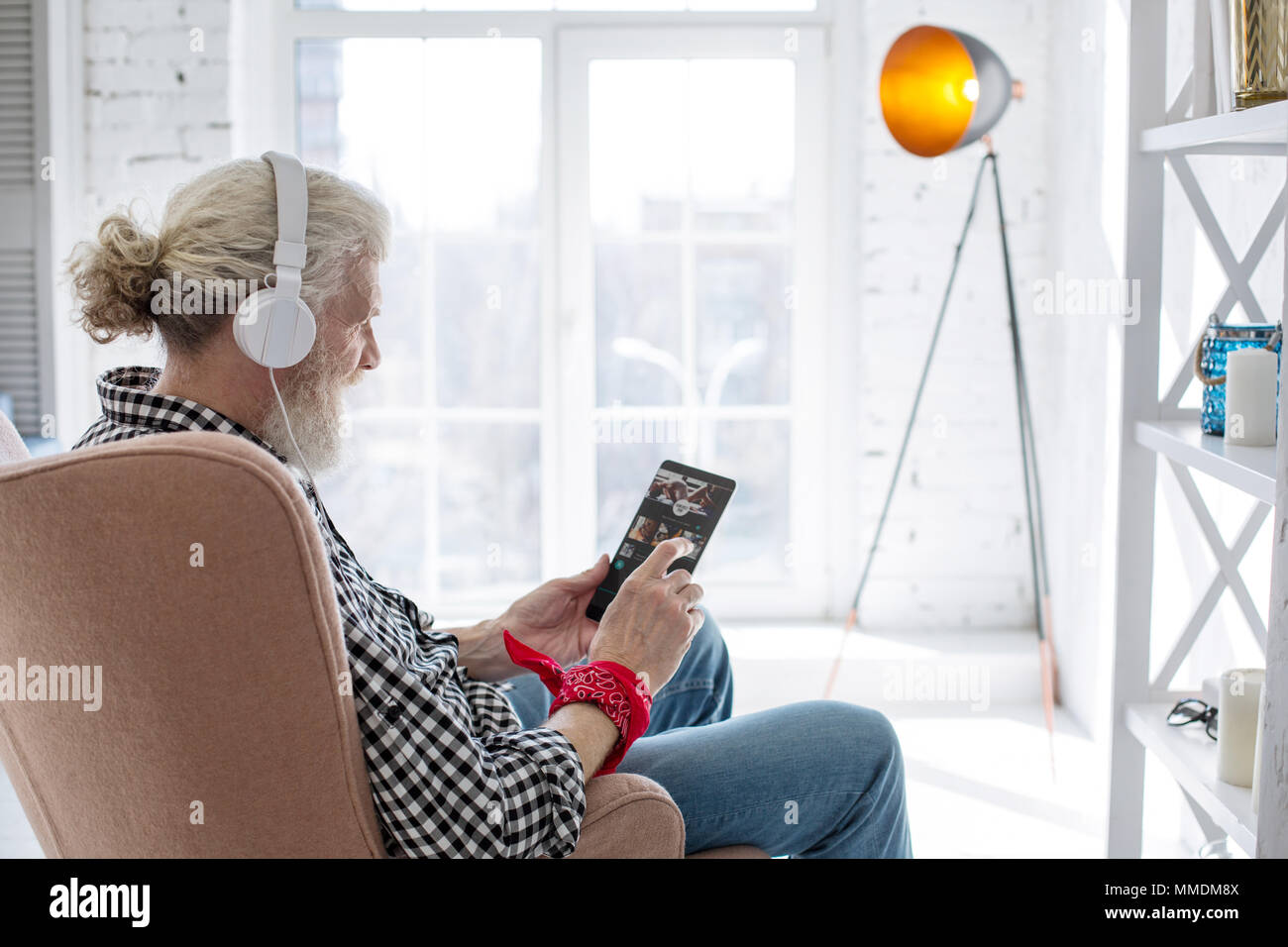 Charming senior man choosing track from playlist - Stock Image