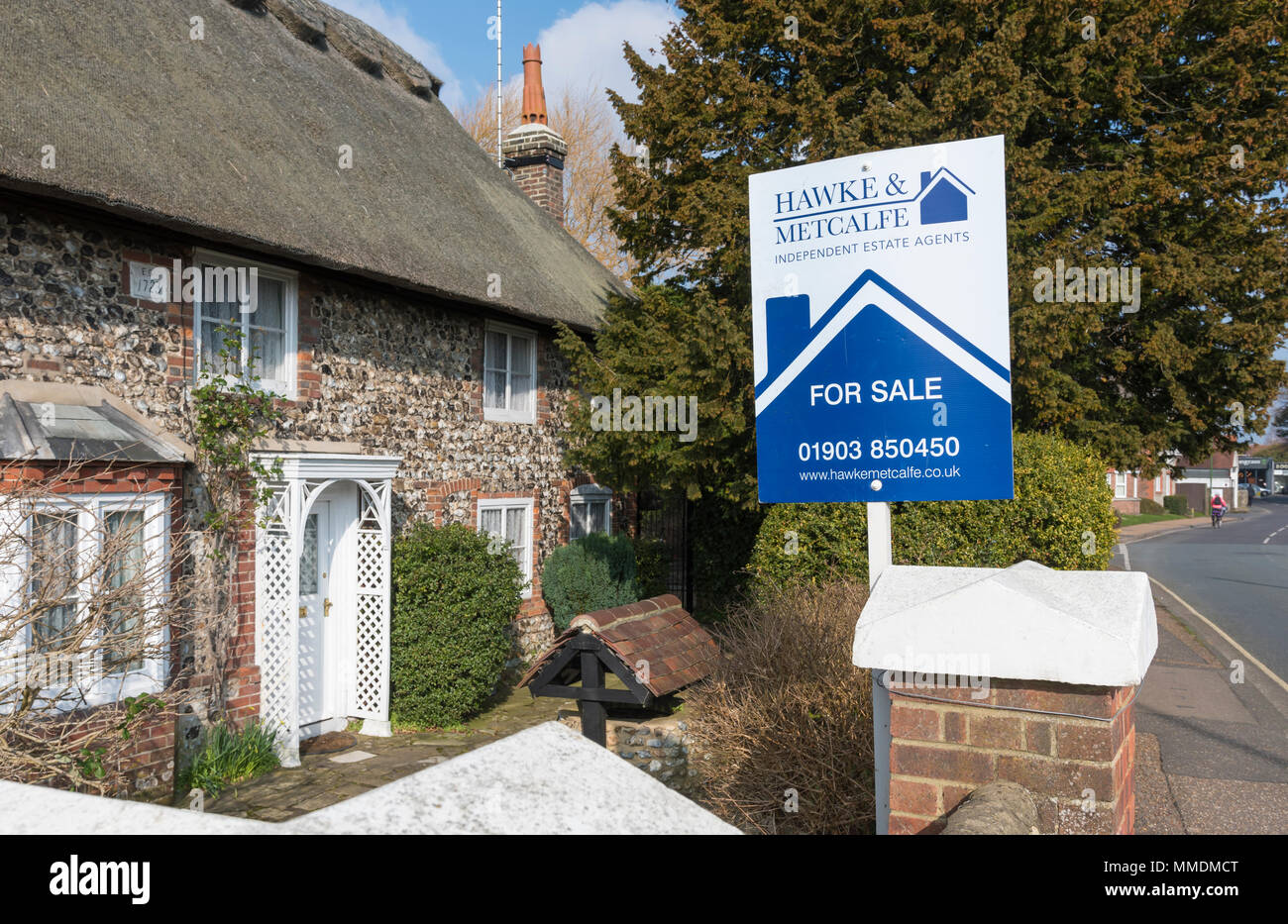 For sale sign from Hawke & Metcalfe estate agents by a cottage for sale in a village in England, UK. - Stock Image