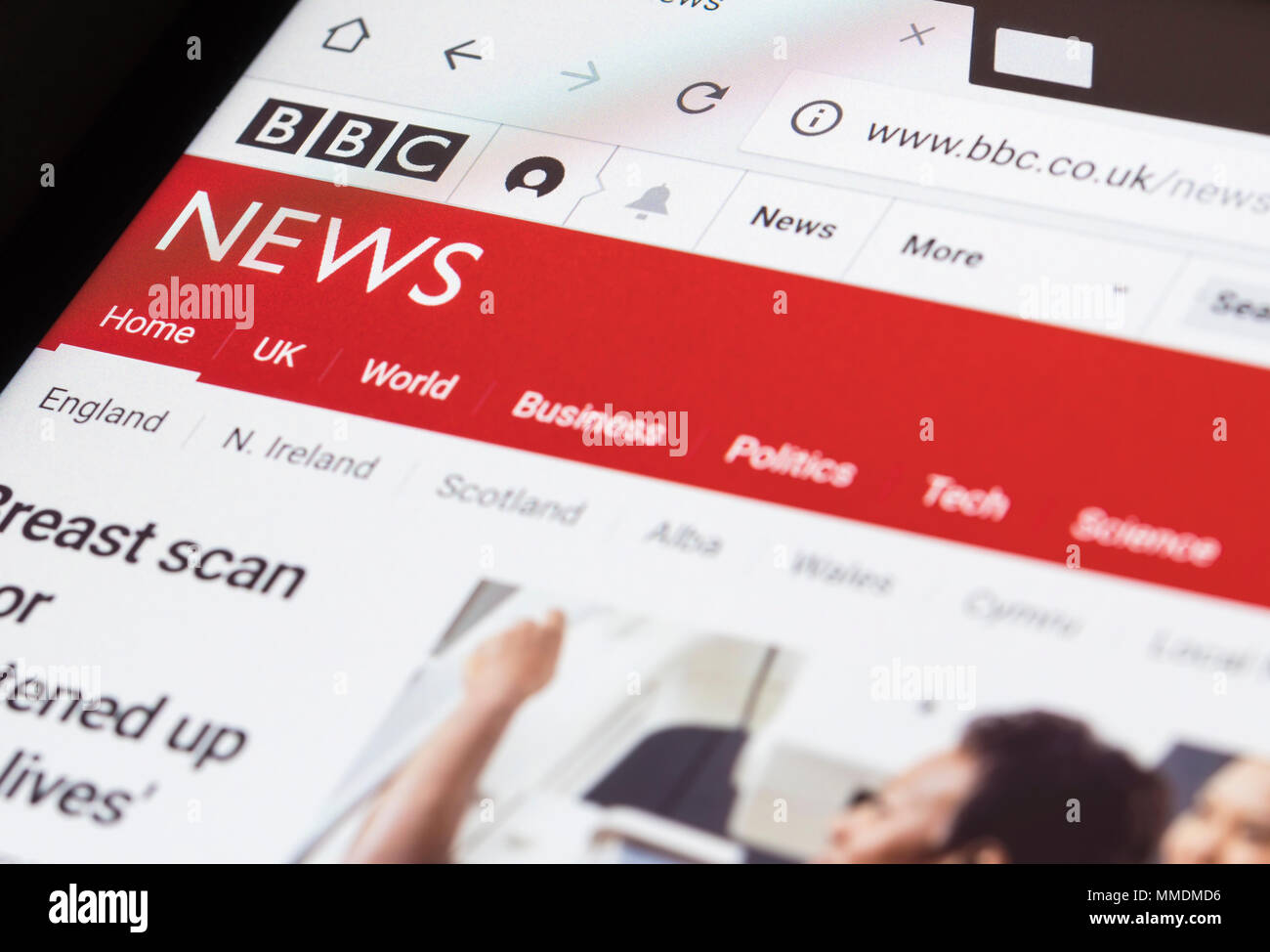 Reading the BBC news website on a tablet. - Stock Image