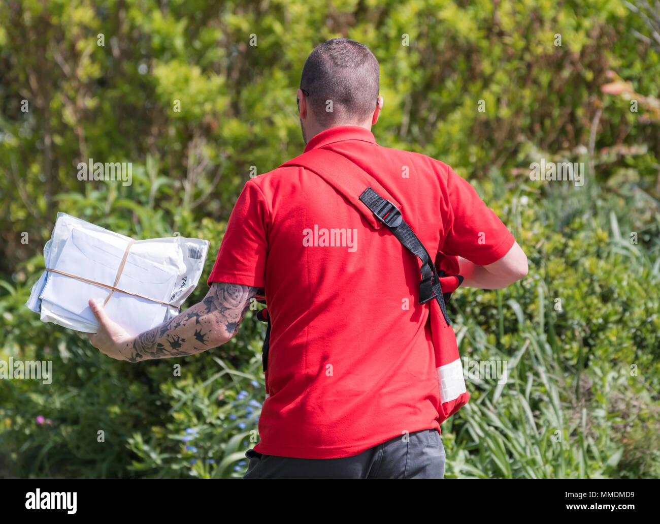 British Royal Mail Postman holding a handful of letters while walking through a park on a sunny day in England, UK. - Stock Image