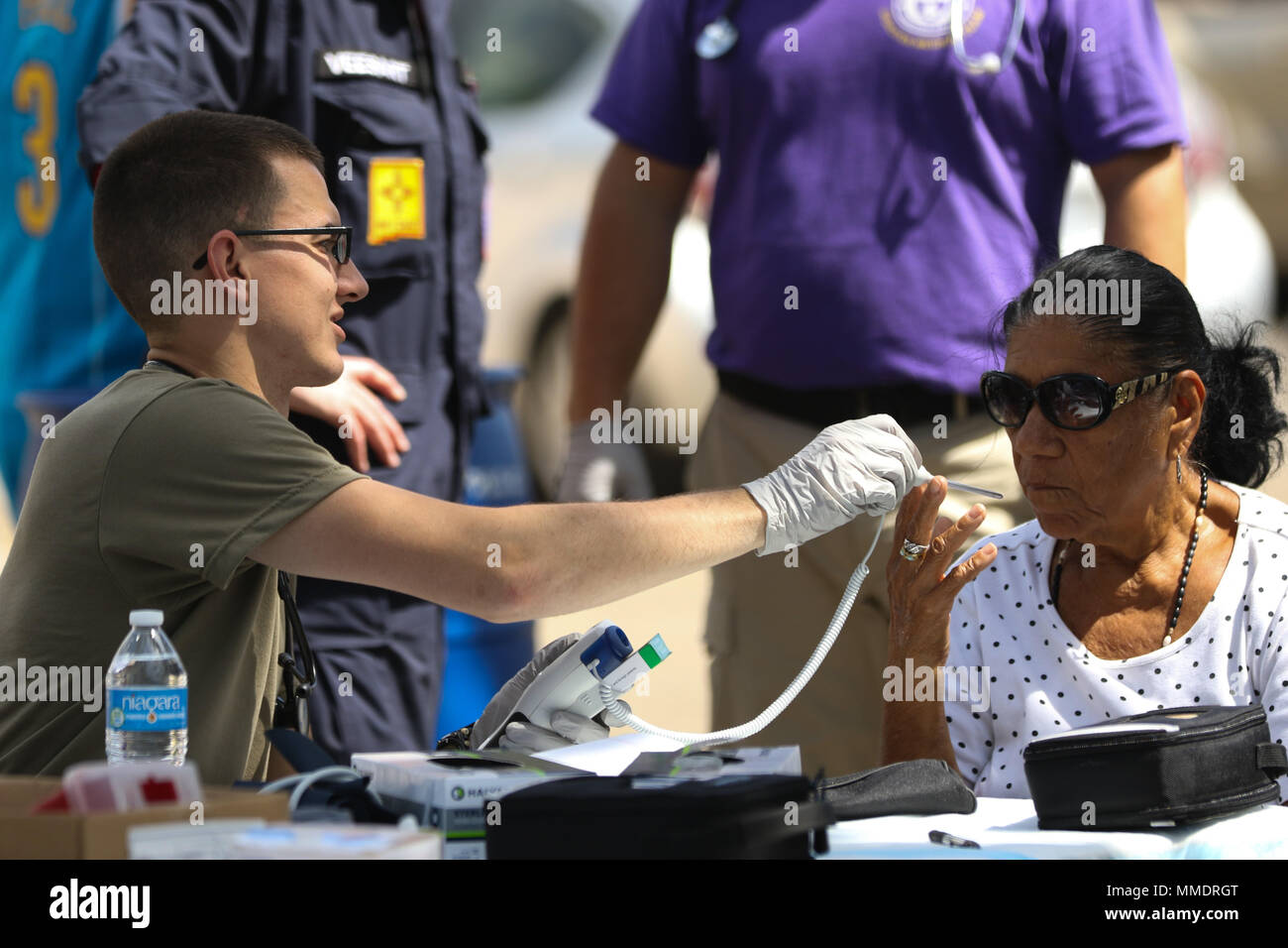 Spc. Jacob Parker, a health care specialist with the Ohio Army National Guard, takes the vital signs of a patient at a temporary medical outreach station set up on a residential street Oct. 21, 2017, in Juana Diaz, Puerto Rico. Parker is part of a Rapid Assessment Team (RAT) that travels to members of the community who need medical attention but are unable to make it to a hospital or aid station due to road closures or lack of transportation following Hurricane Maria. (Ohio National Guard photo by Sgt. Joanna Bradshaw) - Stock Image