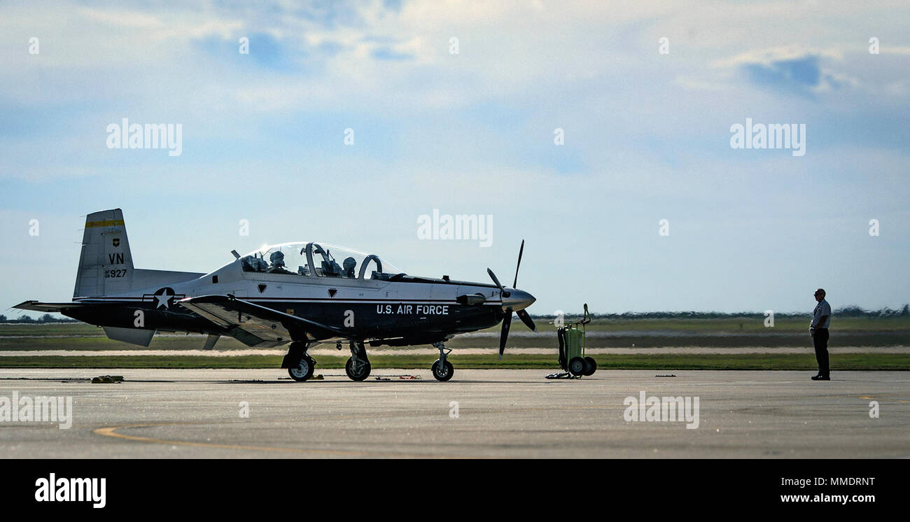 An L3 Communications crew chief leads a T-6 Texan II crew to the active runway at Vance Air Force Base, Oklahoma, Oct. 19. Since 1960, Vance Airmen have partnered with civilian contractors to train tomorrow's military aviators. (U.S. Air Force photo by David Poe) Stock Photo