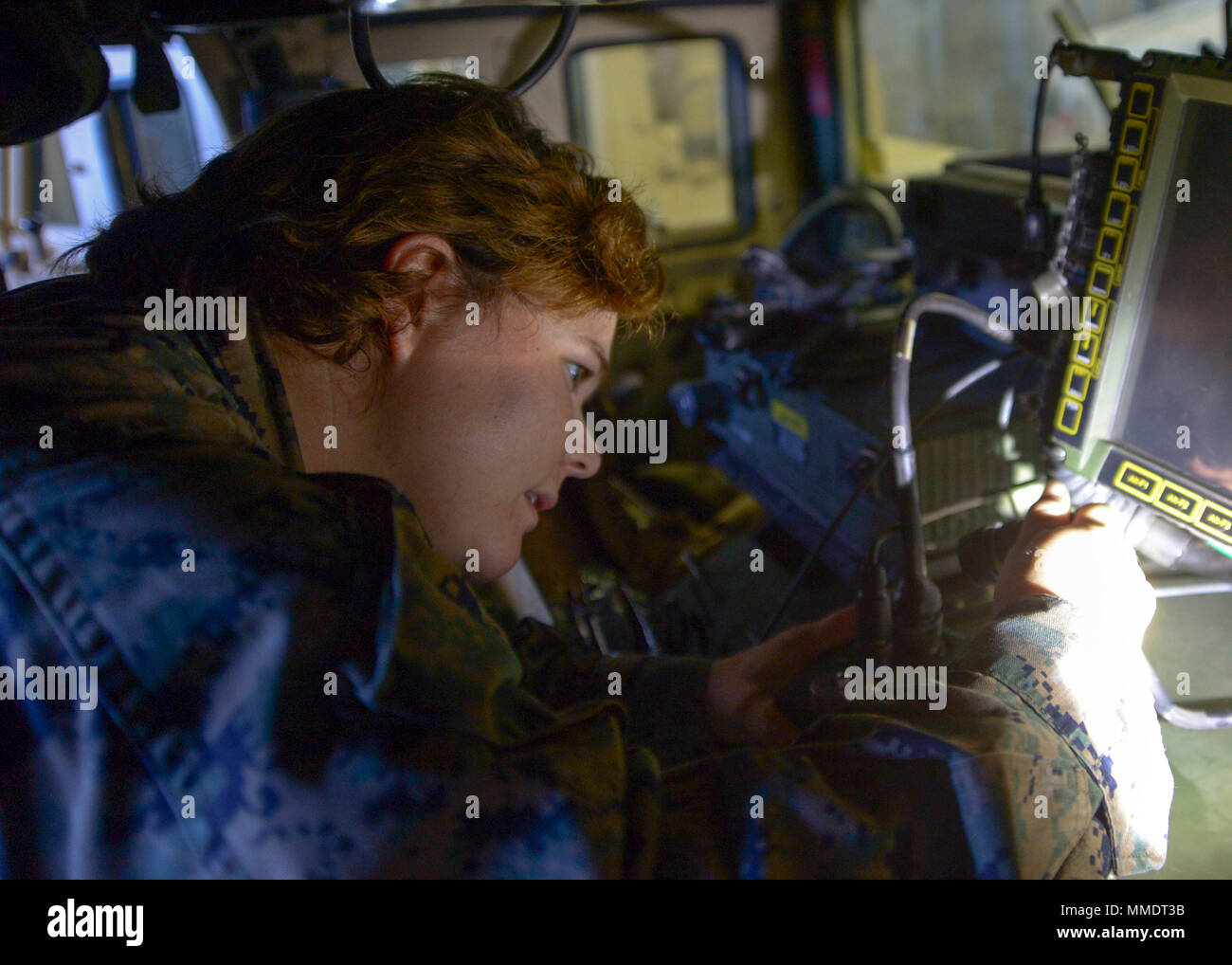 171022-N-NB142-388  PACIFIC OCEAN (Oct. 22, 2017) Marine Sgt. Emily Estelita Larue, assigned to 1st Law Enforcement Battalion, 1st Marine expeditionary Brigade (MEB), installs a Blue Force Tracker in a High Mobility Multipurpose Wheeled Vehicle (HMMWV) aboard the Wasp-class amphibious assault ship USS Essex (LHD 2) during Dawn Blitz 2017.  Dawn Blitz is a scenario-driven exercise designed to train and integrate Navy and Marine Corps units by providing a robust training environment where forces plan and execute an amphibious assault, engage in live-fire events, and establish expeditionary advan - Stock Image