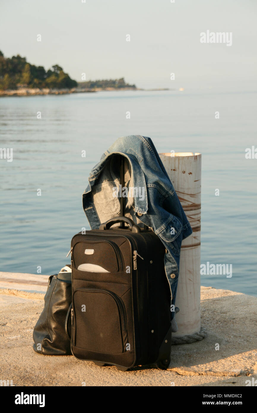 small suitcase and denim jacket with sea view - Stock Image