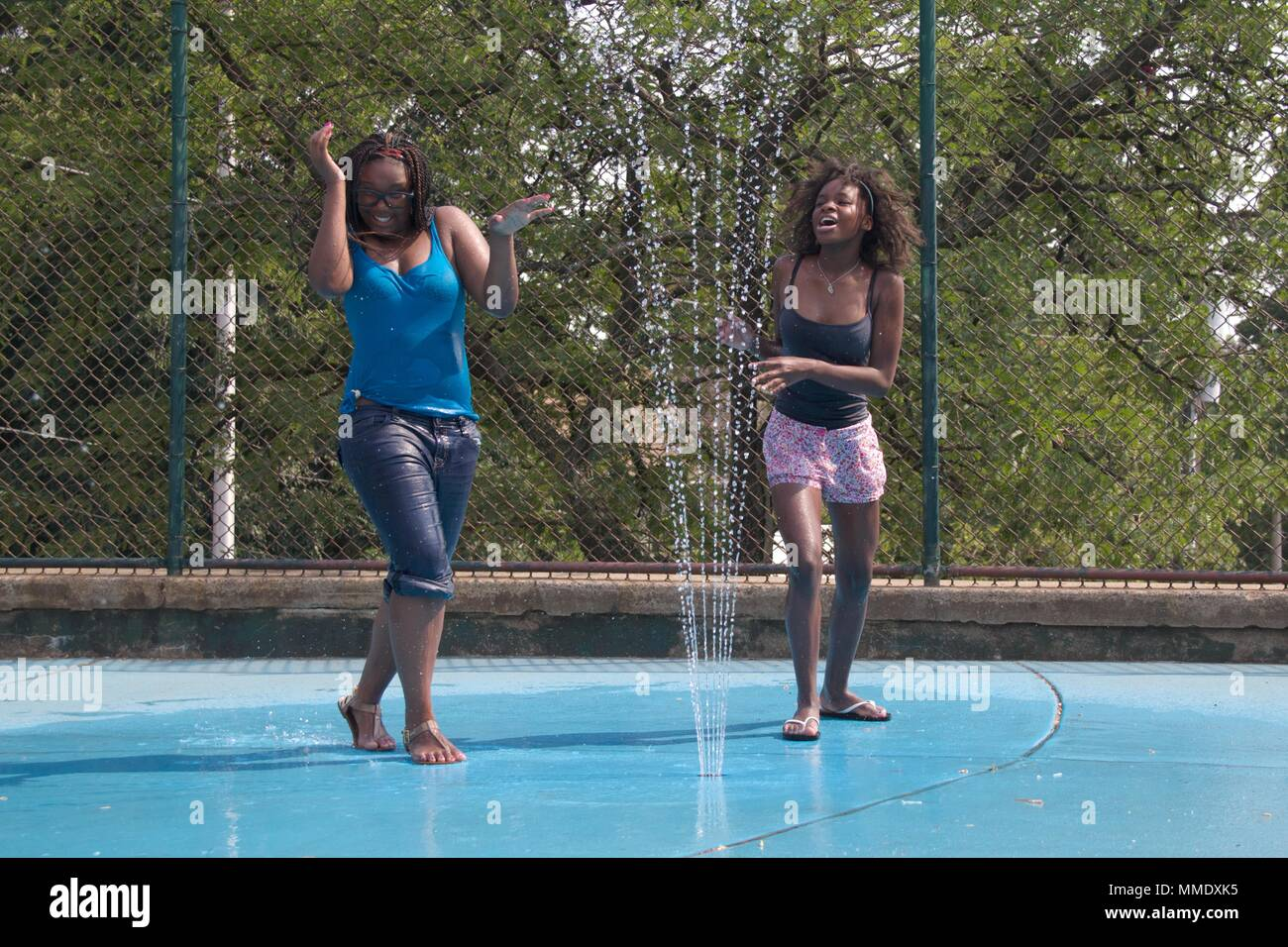 July 7, 2012 - Philadelphia, PA, USA:  Two young black women cool off in one of the city's public spray grounds on a hot summer day. - Stock Image