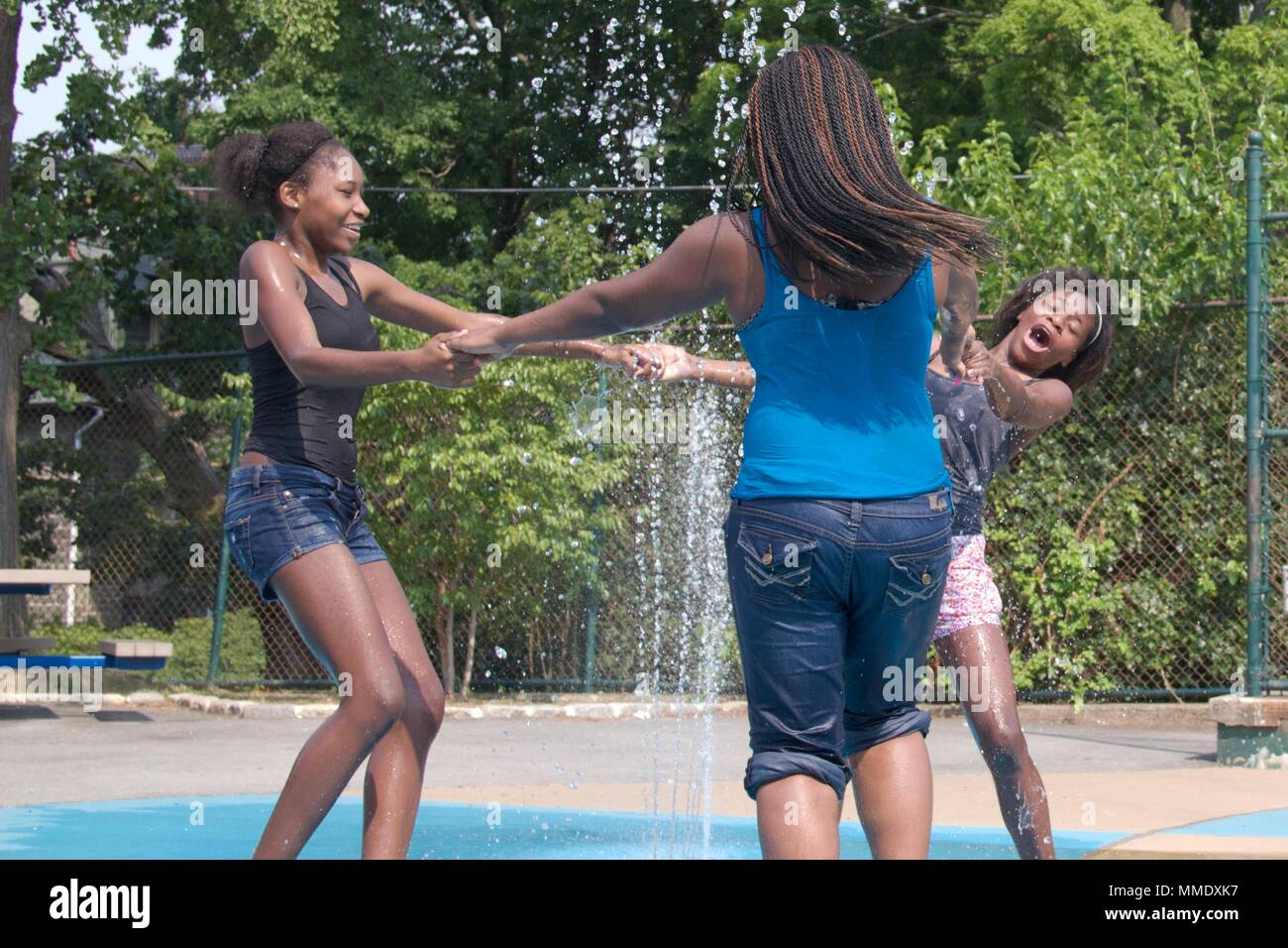 July 7, 2012 - Philadelphia, PA, USA:  Three young black women cool off in one of the city's public spray grounds on a hot summer day. - Stock Image