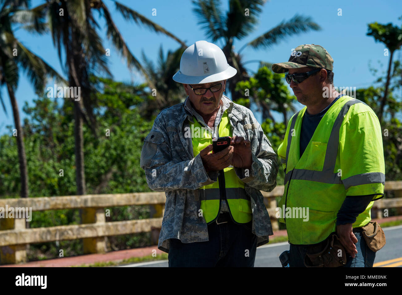 Employees of the Del Valle Group, S.P., take a break after working to repair a bridge damaged during Hurricane Maria in Toa Baja, Puerto Rico,, Oct. 24, 2017. (U.S. Air Force photo by Airman 1st Class Nicholas Dutton) - Stock Image