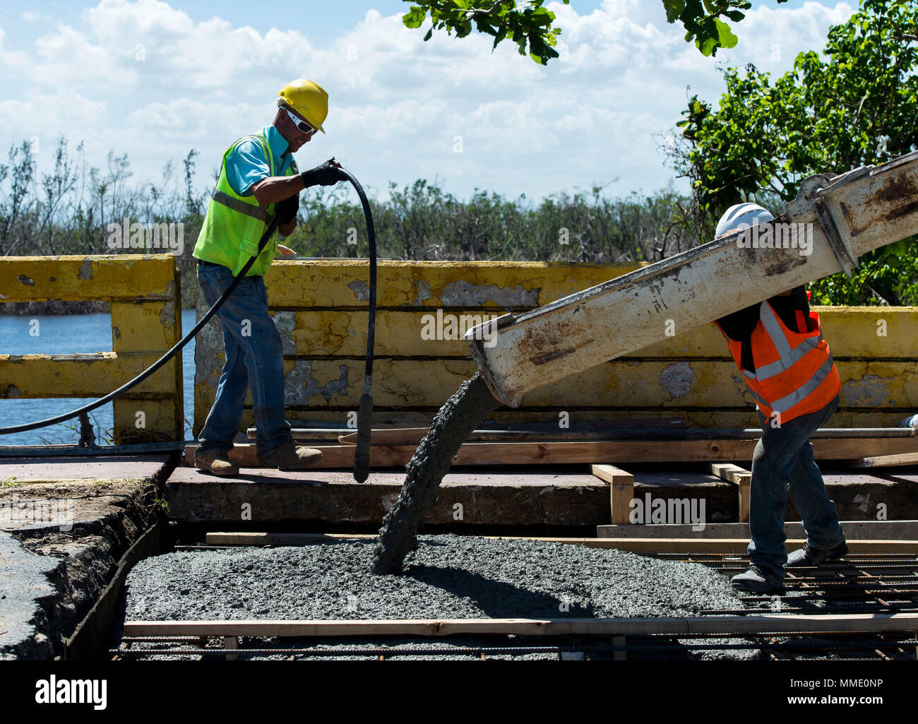 Employees of the Del Valle Group, S.P., pour concrete  to repair a bridge damaged during Hurricane Maria in Toa Baja, Puerto Rico, Oct. 24, 2017. (U.S. Air Force photo by Airman 1st Class Nicholas Dutton) - Stock Image