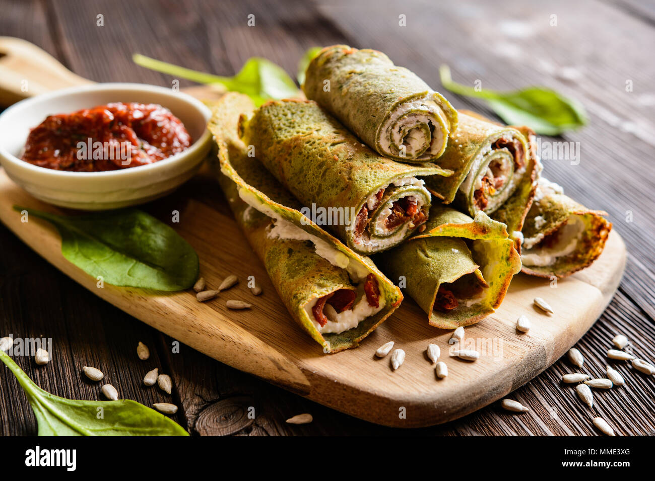 Savory spinach pancakes stuffed with Feta cheese, curd, sun dried tomato and sunflower seeds - Stock Image