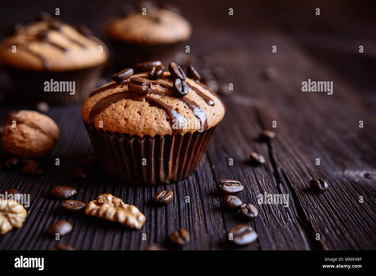 Coffee muffins with grated walnut and topped with chocolate - Stock Image