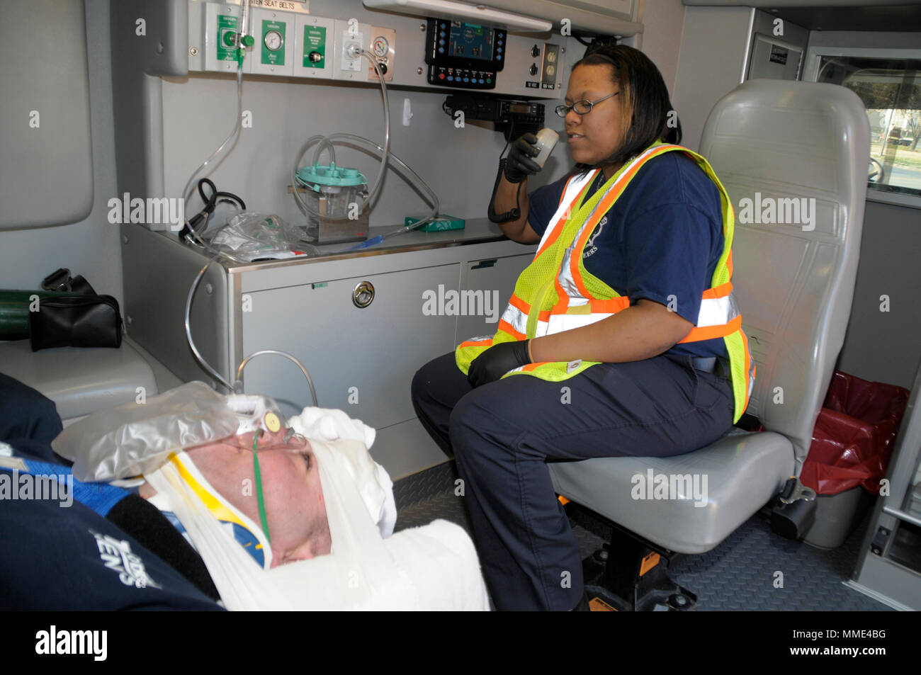 medic  relays the victim's condition to a hospital  via a 2 way radio  (model released) - Stock Image