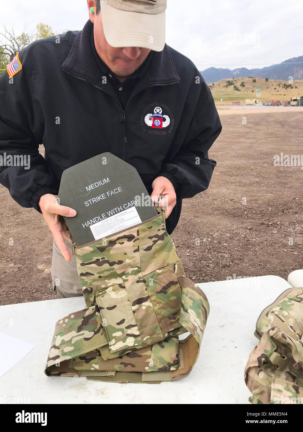 Michael Spencer, a new equipment trainer from Project Manager Soldier Protection Individual Equipment at Fort Bragg, N.C., demonstrates how to transfer ballistic plates from the Modular Scalable Vest (MSV) to a plate carrier configuration enclosed within the MSV, during the final round of field-testing of the vest at Fort Carson, Colo., Oct. 18, 2017. Once this evaluation is complete, the vest will go into production and is expected to reach Soldiers in the field by summer of next year. (U.S. Army photo by Staff Sgt. Lance Pounds, 71st Ordnance Group (EOD), Public Affairs) - Stock Image