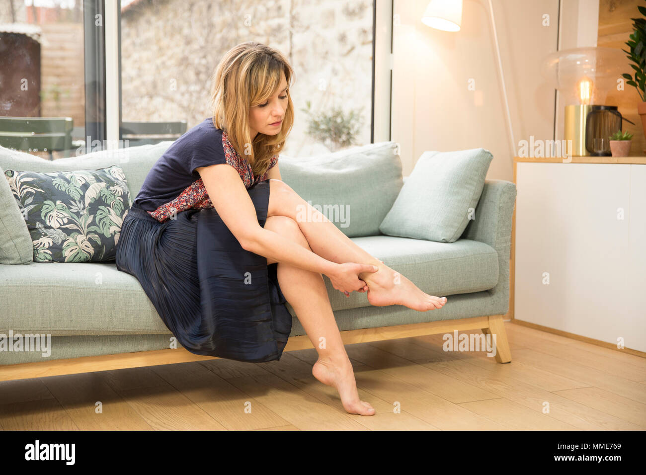 WOMAN WITH ANKLE PAIN - Stock Image