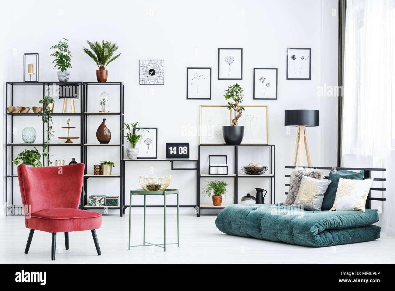 Table between red chair and green futon in home office interior with posters and plants - Stock Image