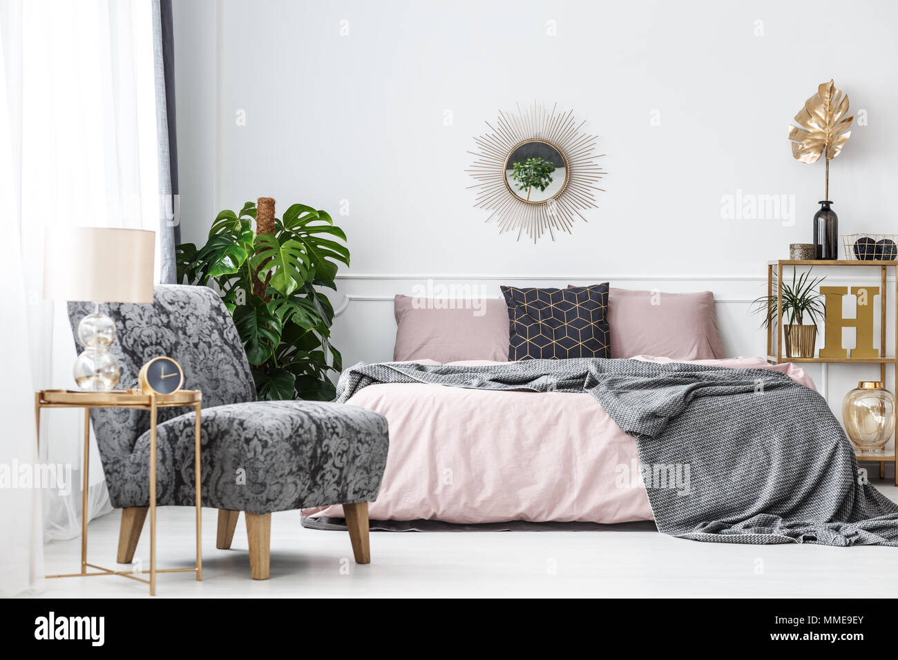 White Hotel Bedroom Interior With Pink Gray And Gold Accents Such As A Mirror Armchair Or Table Stock Photo Alamy