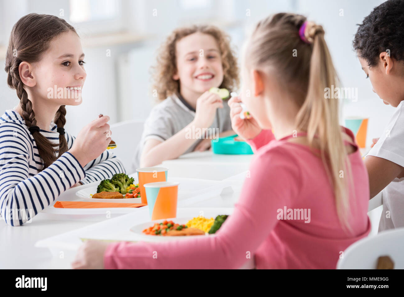 Smiling girl eating vegetables during lunch break with friends at school - Stock Image