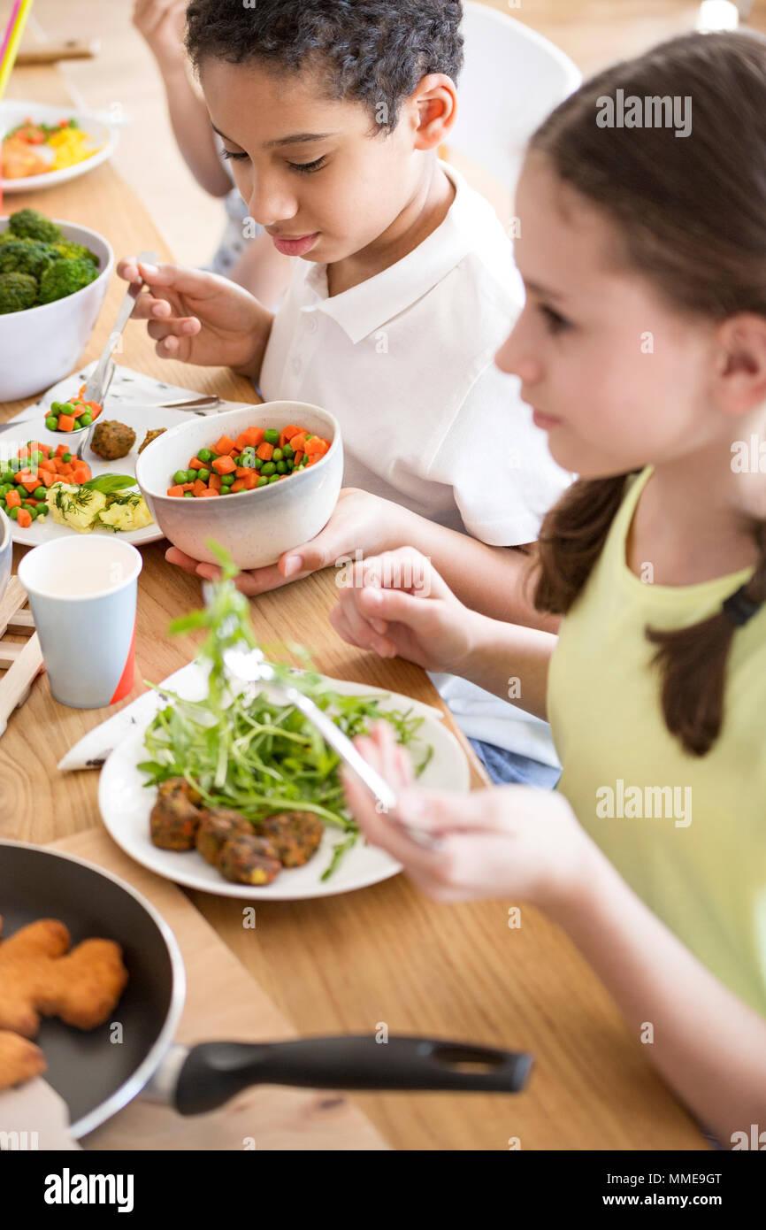 High angle of children eating vegetables for dinner at school - Stock Image
