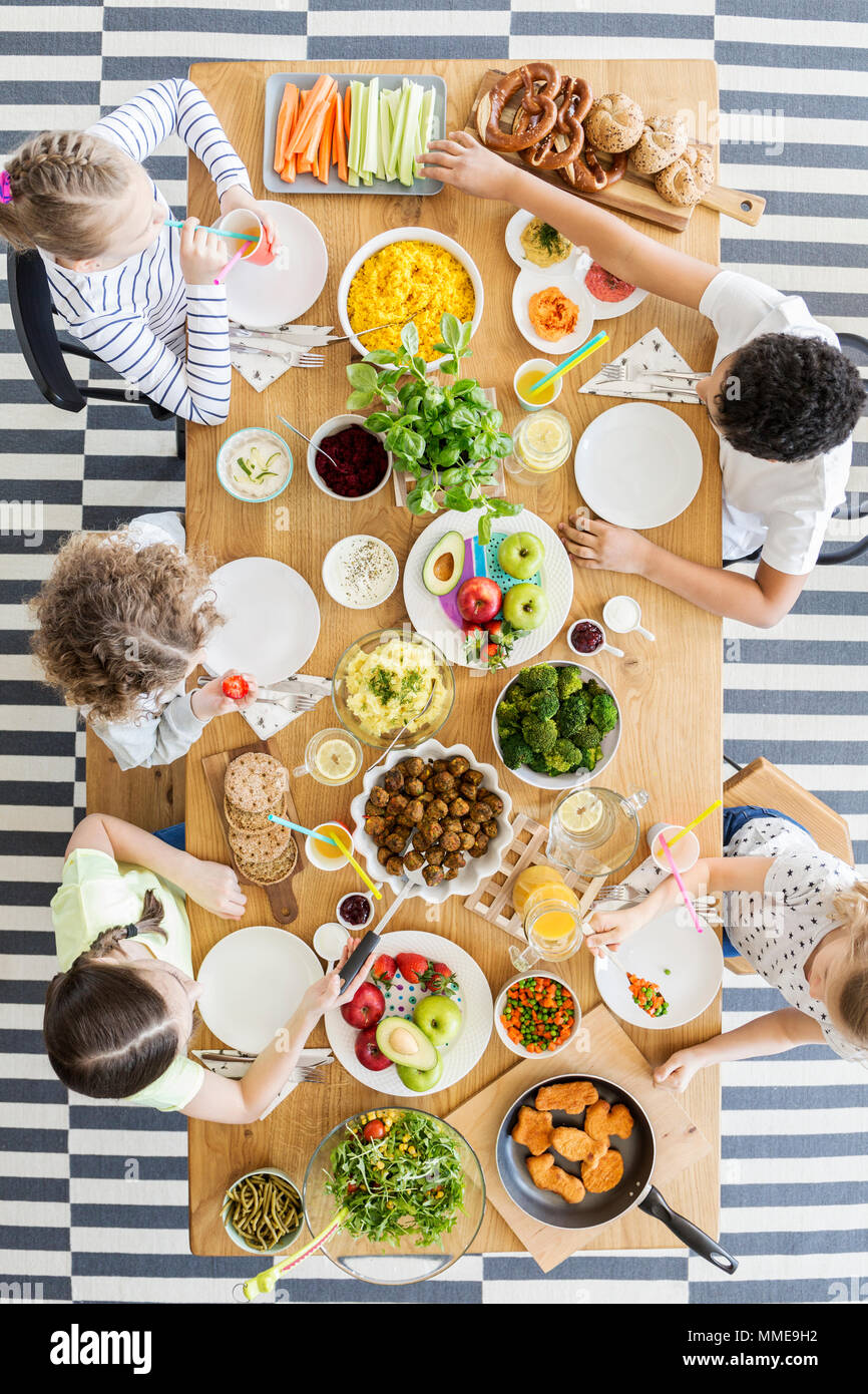 Top view on children eating healthy food at table during birthday party - Stock Image