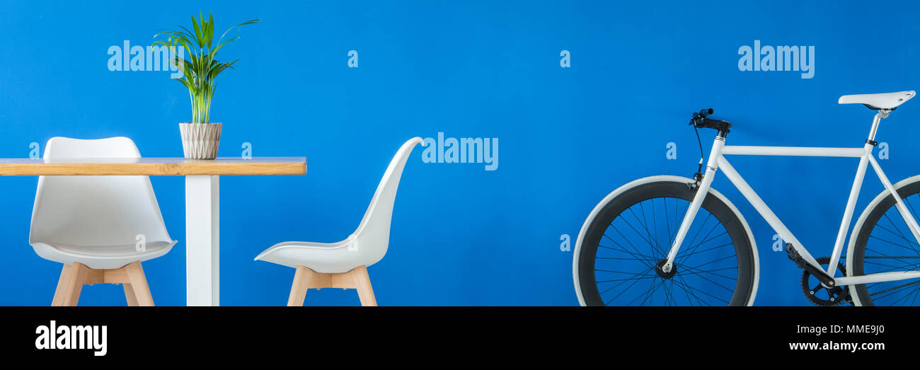 Panorama of a hipster bike by a royal blue wall and a white wooden dining set in a modern apartment interior Stock Photo