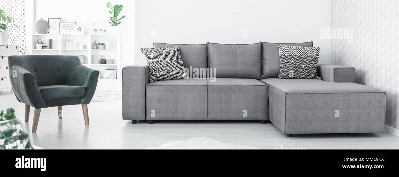 Grey corner sofa with two black and white cushions and green ...