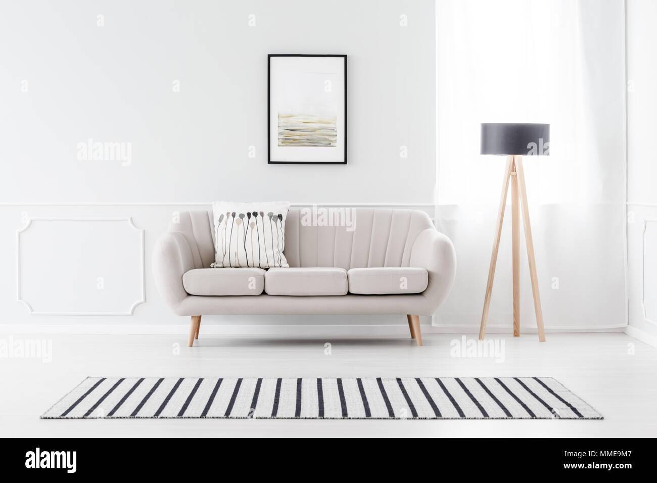 Beige couch standing against white wall with molding and watercolor ...