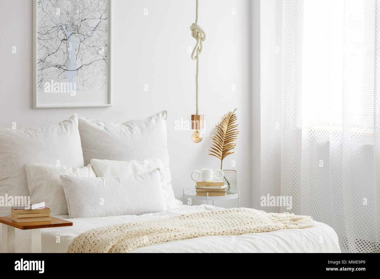 simple bulb lamp on a rope hanging above bed with white bedclothes books and gold fern leaf on an end table in white bedroom interior - Hanging End Tables
