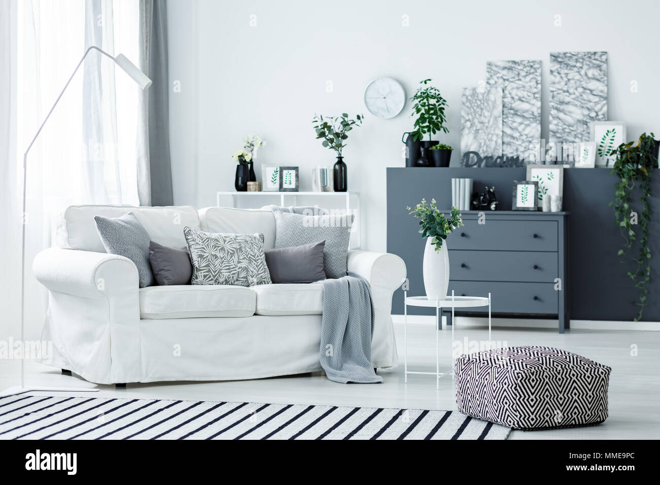 White, comfy sofa, pouf, plants and grey accents in a modern living room interior - Stock Image