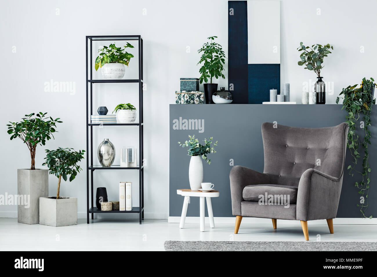 Modern sitting area interior with a comfy armchair, metal shelf and plants - Stock Image