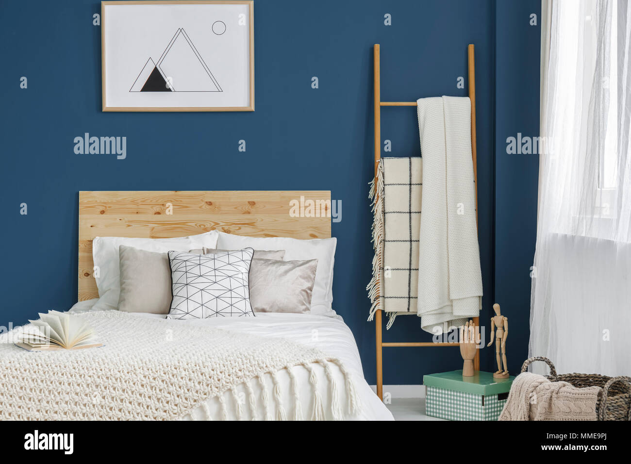 Double bed with wooden bedhead standing in blue room interior with window and simple poster on the wall - Stock Image