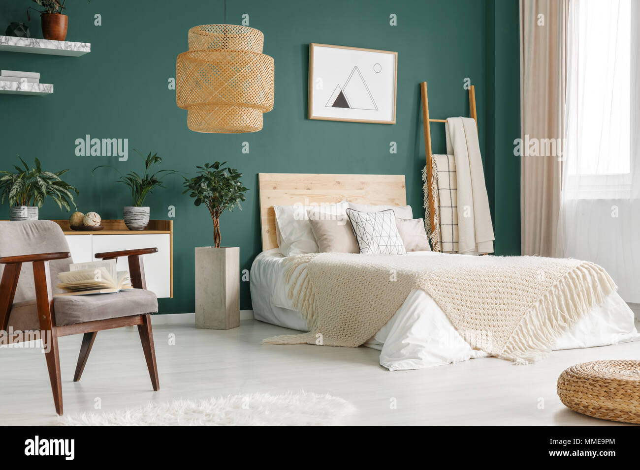 Green bedroom interior with king-size bed, potted plants and big, wicker lamp - Stock Image