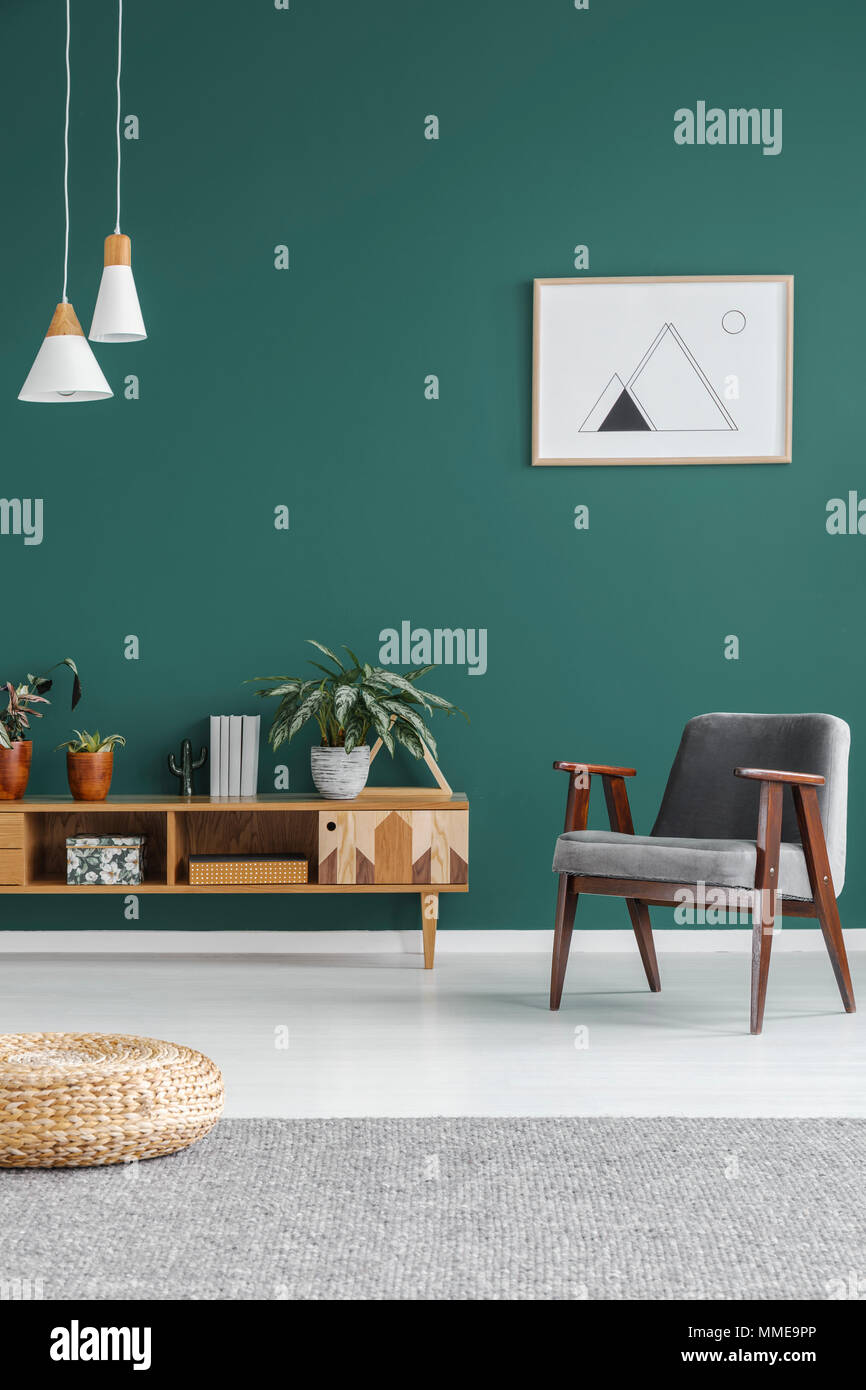 Simple geometric poster hanging on the wall in green living room interior with grey armchair, wooden cupboard and fresh plants - Stock Image