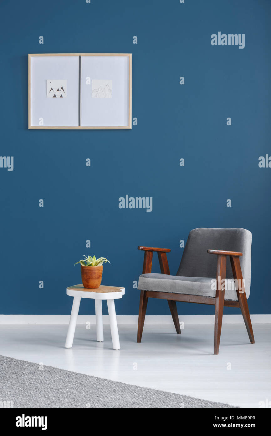 Grey armchair placed by a wooden end table with fresh plant in blue room interior with minimal poster - Stock Image